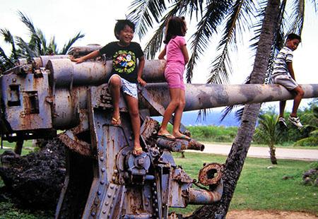 Truk (Micronesia) bambini giocano su un cannone giapponese...